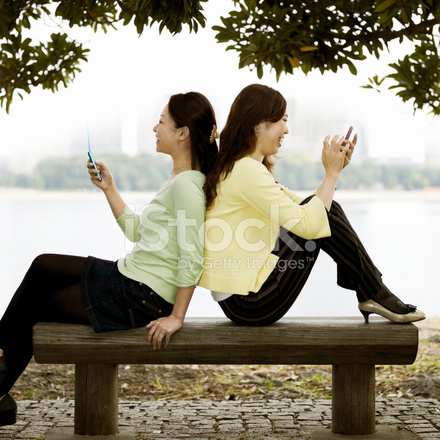 Women Sitting Against One Another And Texting Stock Photos