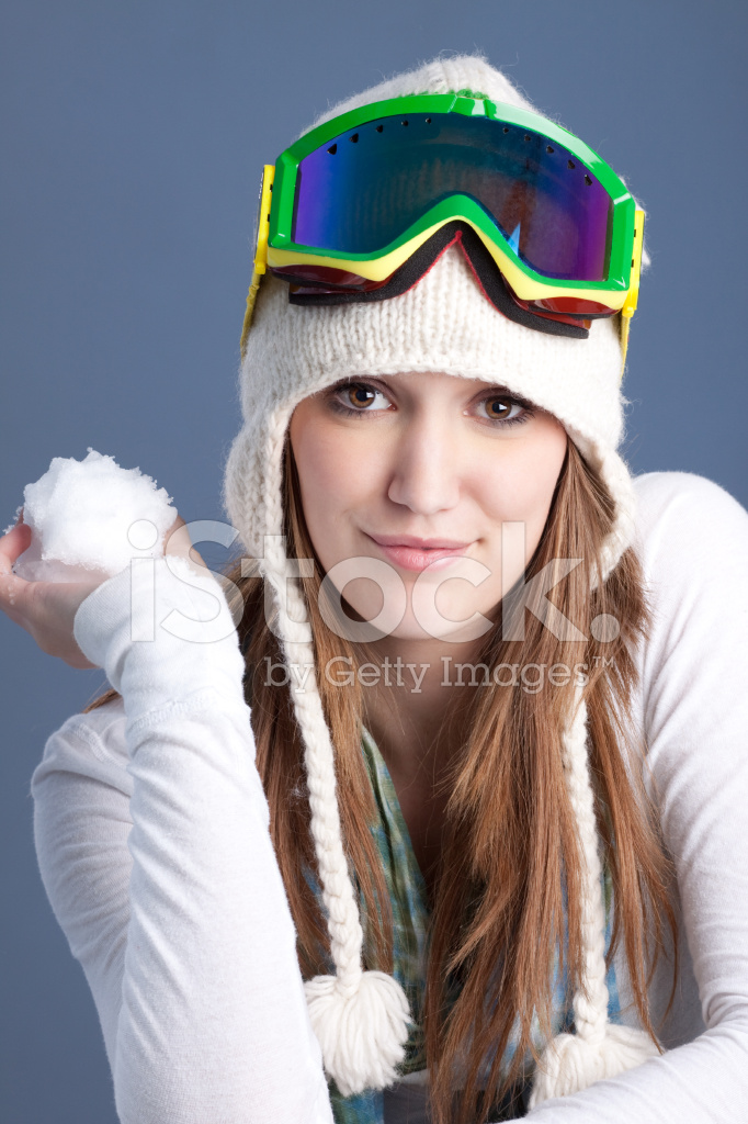 Woman Holding Snow Wearing Winter Hat And Ski Goggles