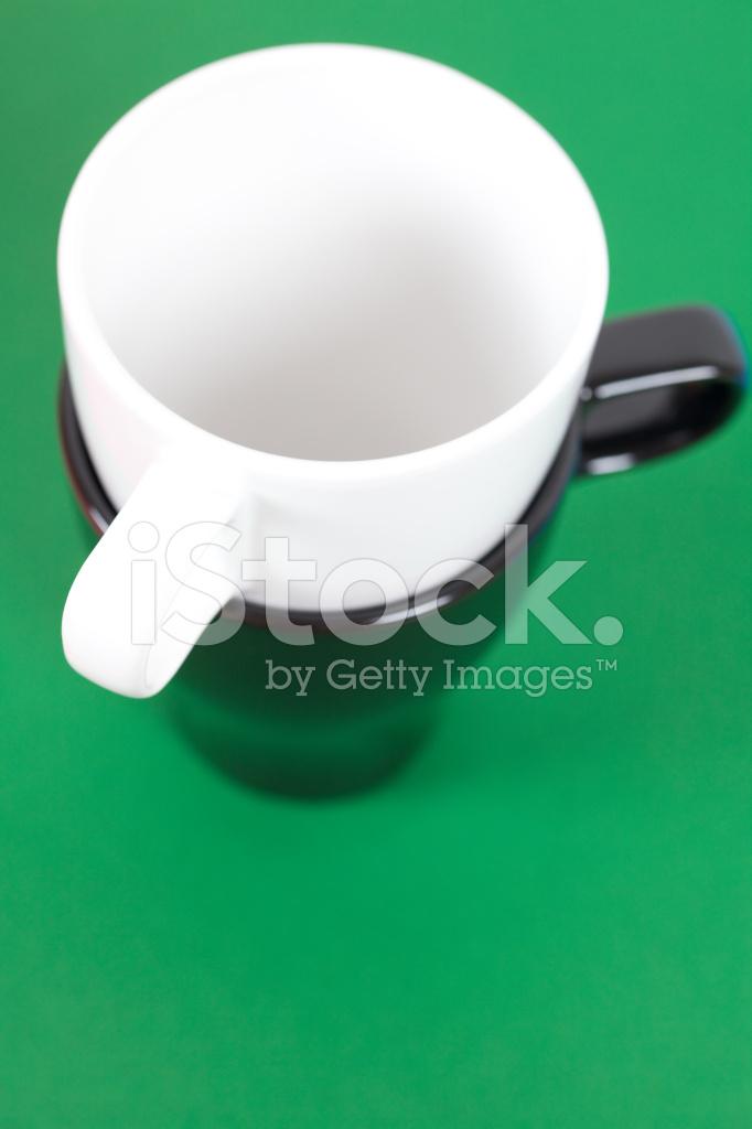 Tazza Bianco E Nero In Piedi Su Uno Sfondo Verde Fotografie Stock