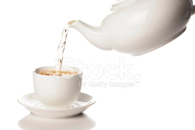 Weiße Teekanne grüner aus weiße teekanne in einen becher gießen stockfotos