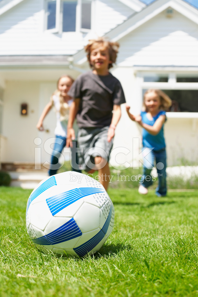kids playing soccer in the backyard stock photos
