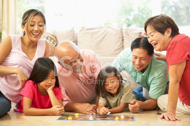 Grupo De Familiares Jugar Juego De Mesa En Casa Fotografias De