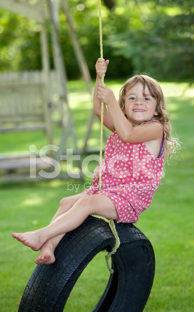 Süße Junge Mädchen Auf Der Reifen Schaukel Stockfotos