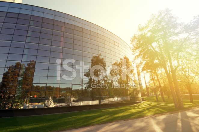 modern glass building surrounded by trees at sunset stock photos