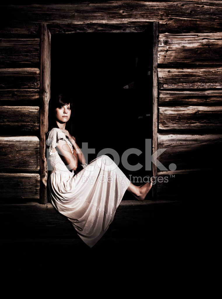 Woman Sitting In An Old Cabin Window Stock Photos