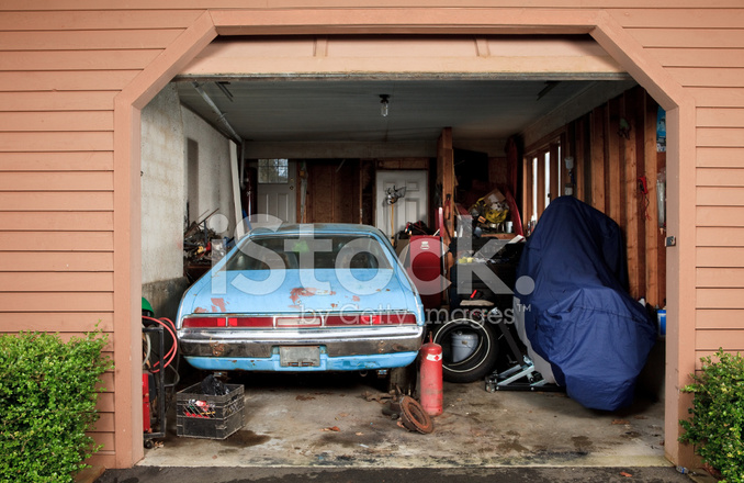 Small Garage Filled With A Car Motorcycle And Tools Stock