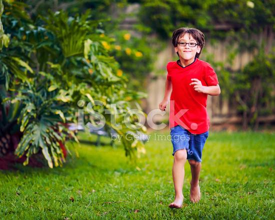 Niño Corriendo En El Patio Trasero Fotografías De Stock