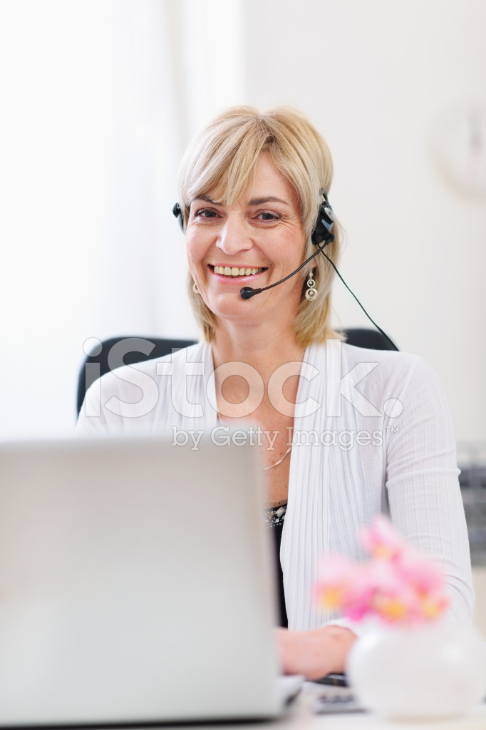 Smiling Senior Business Woman With Headset Working On Laptop