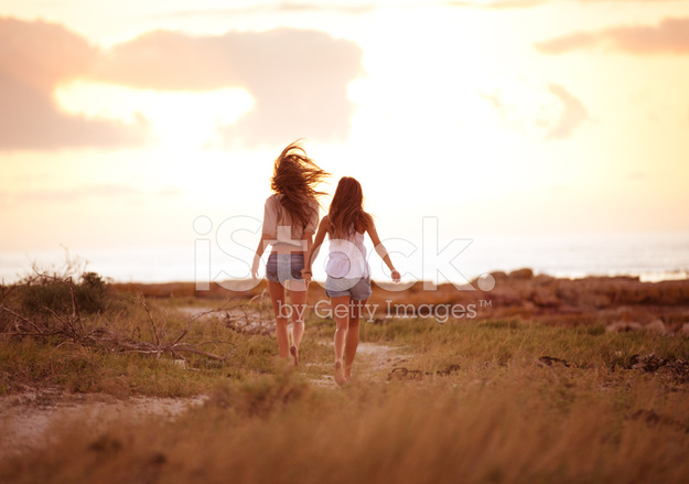 Best Friends Running Together Into The Sunset Holding