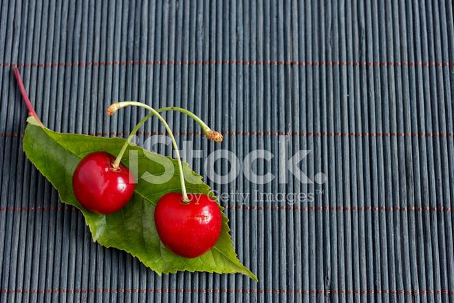 Zwei Frischen Kirschen Und Ein Blatt Auf Bambus Tischdecke