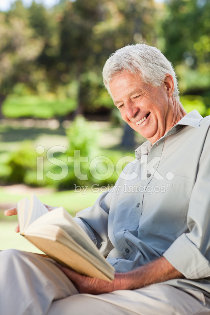 Old Man Laughing And Reading Book Stock Photos