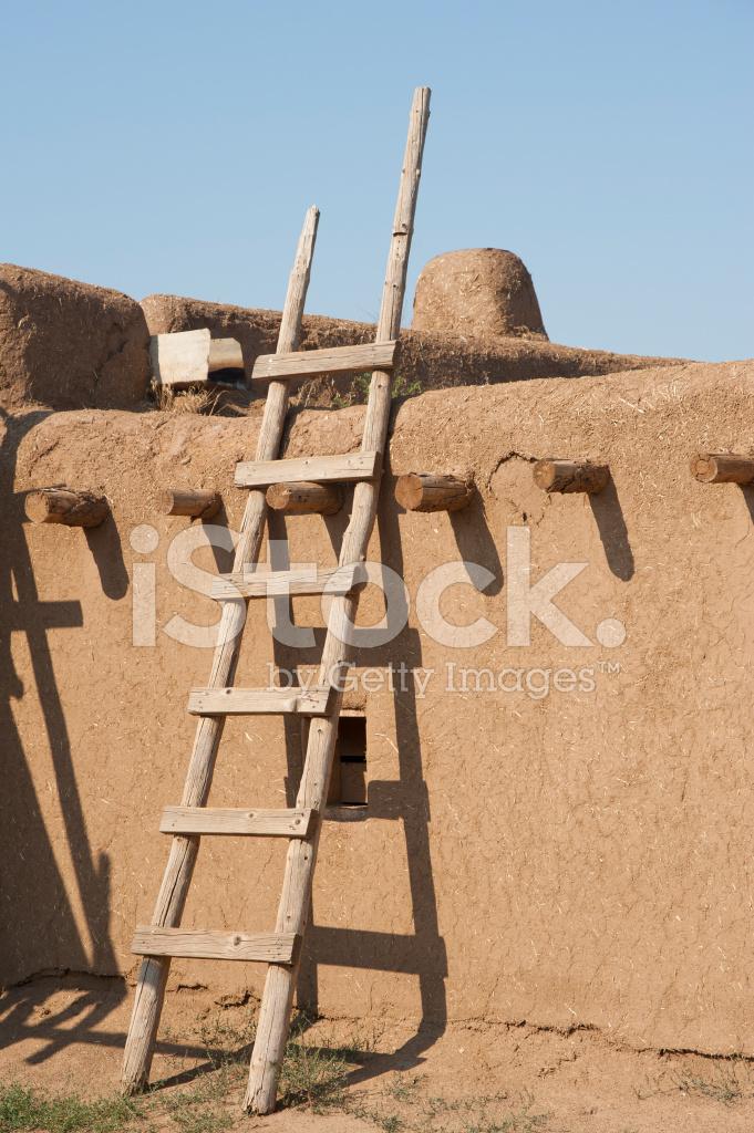 Ladder on adobe pueblo building stock photos for Adobe construction pueblo co