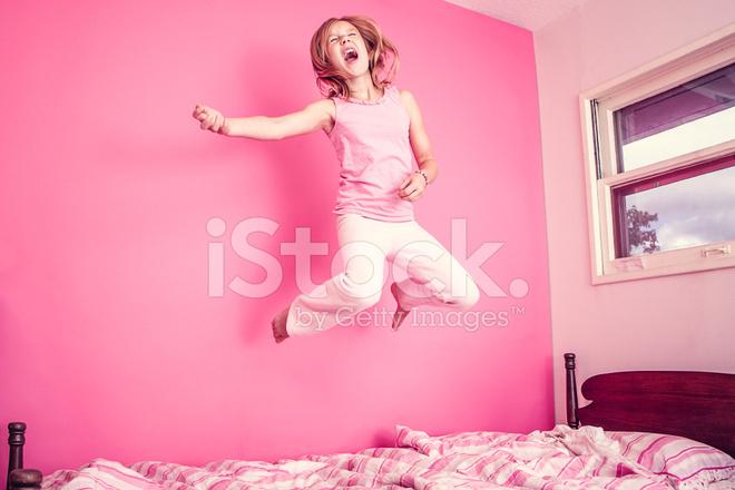 Meisje springen op bed in roze kamer stockfotos freeimages.com