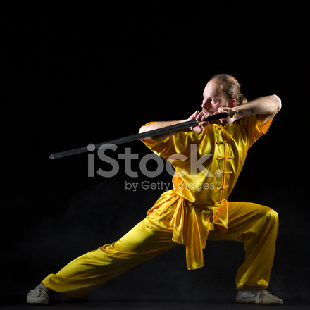 Kung Fu Fighting Position With Jian Sword on Dark Background