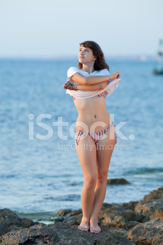 Bikini babes undressing Girl Undresses On Rocky Seashore In Evening Time Stock Photos Freeimages Com