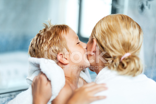 little boy kissing his mother in the bathroom