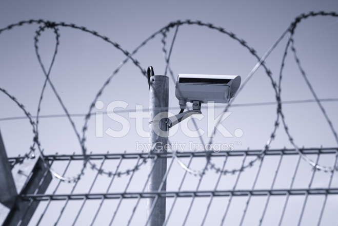 Security camera behind barbed wire stock photos