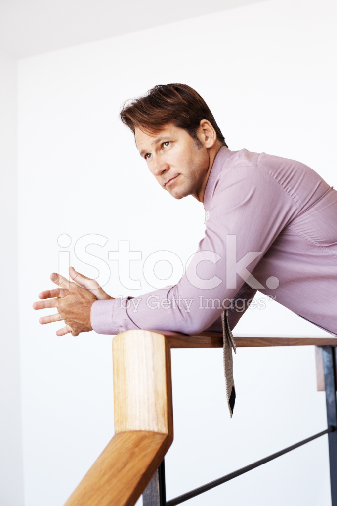 young businessman leaning on railing and looking away stock photos