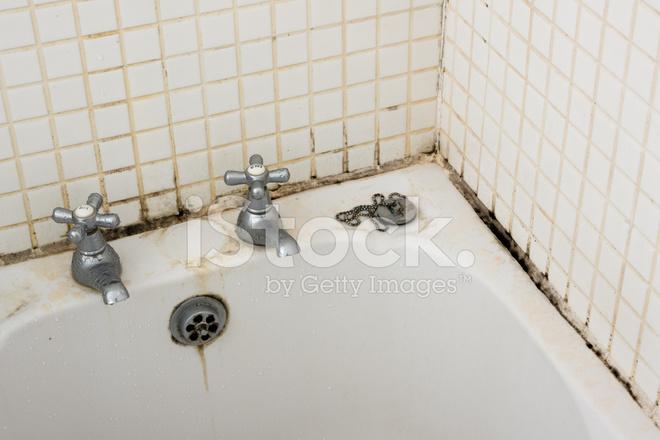 Bagno sporco e muffa sulla stuccatura e piastrelle vicino rubinetti