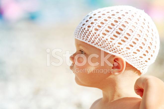 Nieuwsgierig meisje van de baby van de kaukasische in witte hoed op