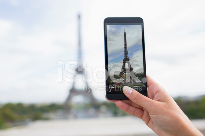 woman in paris taking pictures eiffel tower with cell phone stock photos. Black Bedroom Furniture Sets. Home Design Ideas