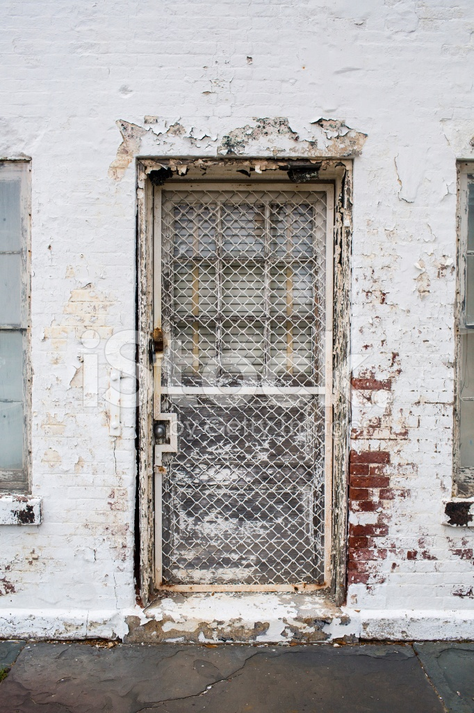 Chain Link Security Door On Old White Exterior Wall Stock Photos