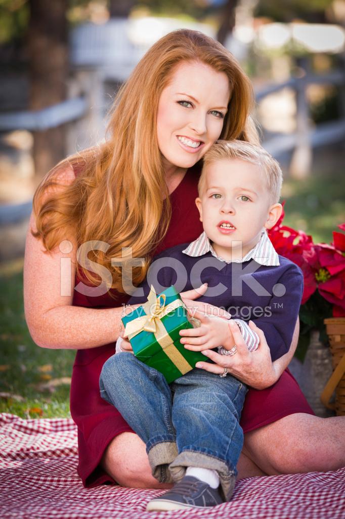 Kleiner Junge Hält Weihnachtsgeschenk MIT Seiner Mutter Im Park ...