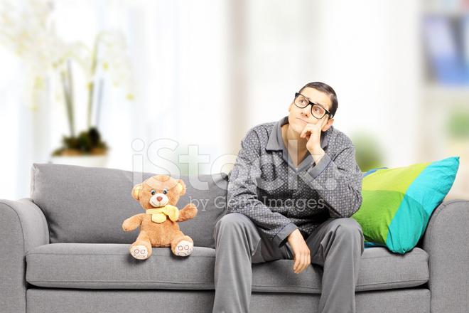 Giovane uomo in pigiama pensando seduto sul divano di casa - Divano di istanbul ...