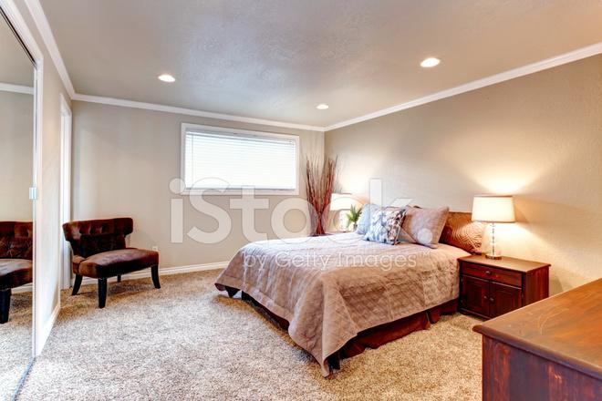 Slaapkamer Met Tapijt : Gezellige bruine tinten slaapkamer met houten meubilair en zachte
