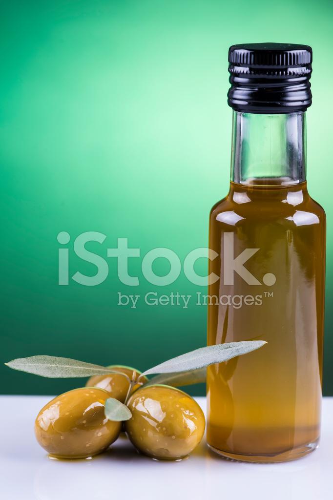 Bottiglia Di Olio Di Oliva E Olive Su Sfondo Verde Fotografie Stock