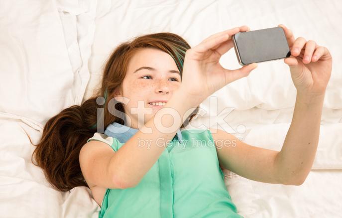 Teenage Girl Shooting Selfie In Bed Stock Photos