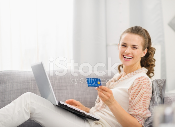 happy housewife laying on sofa with laptop and credit card stock