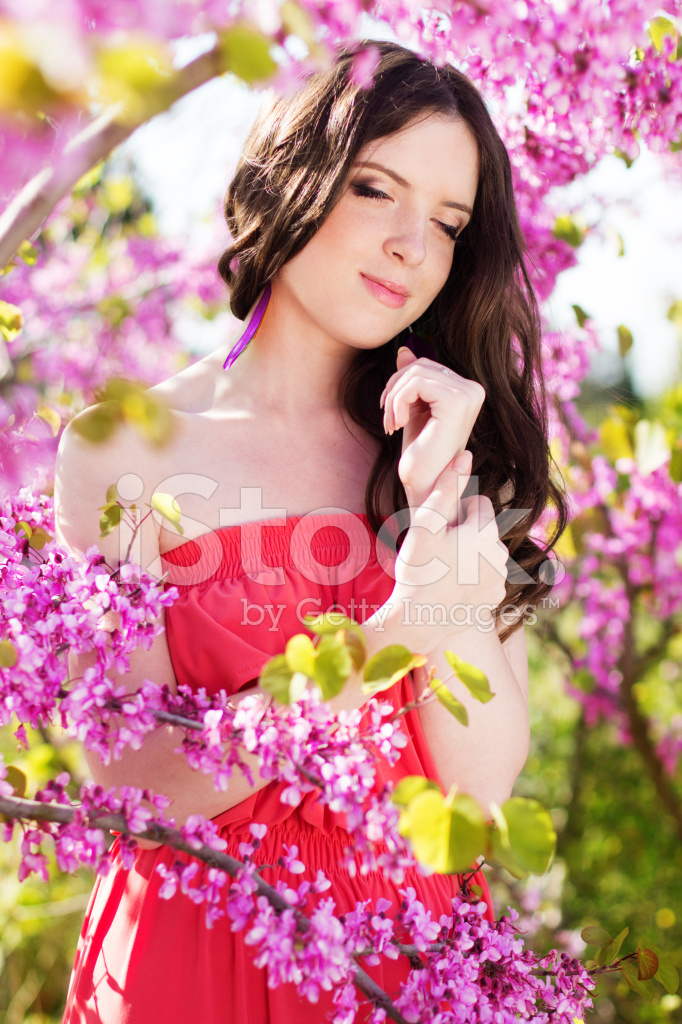 pretty girl in spring park with pink flowers stock photos