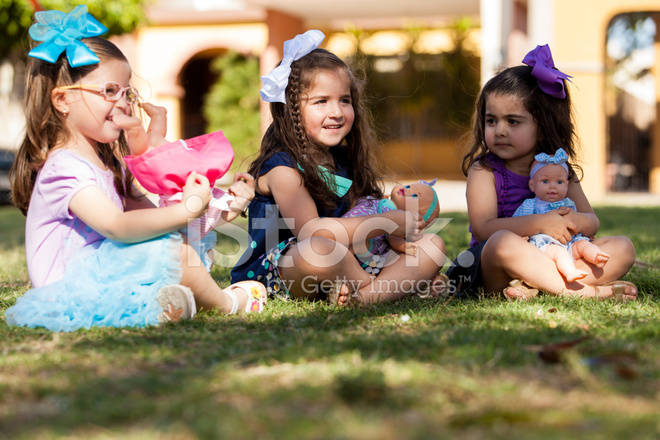 Little Sisters Playing With Dolls Stock Photos