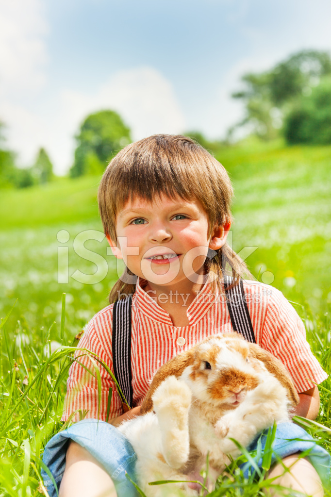Small Boy Hugging Rabbit IN Green Field Stock Photos