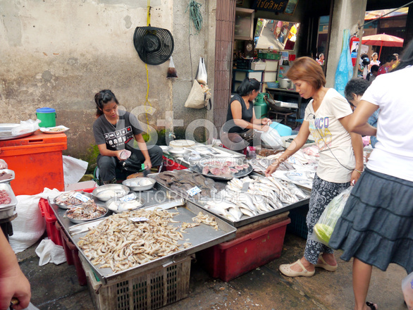 Unidentified woman selling fish on the local market stock for Local fish market