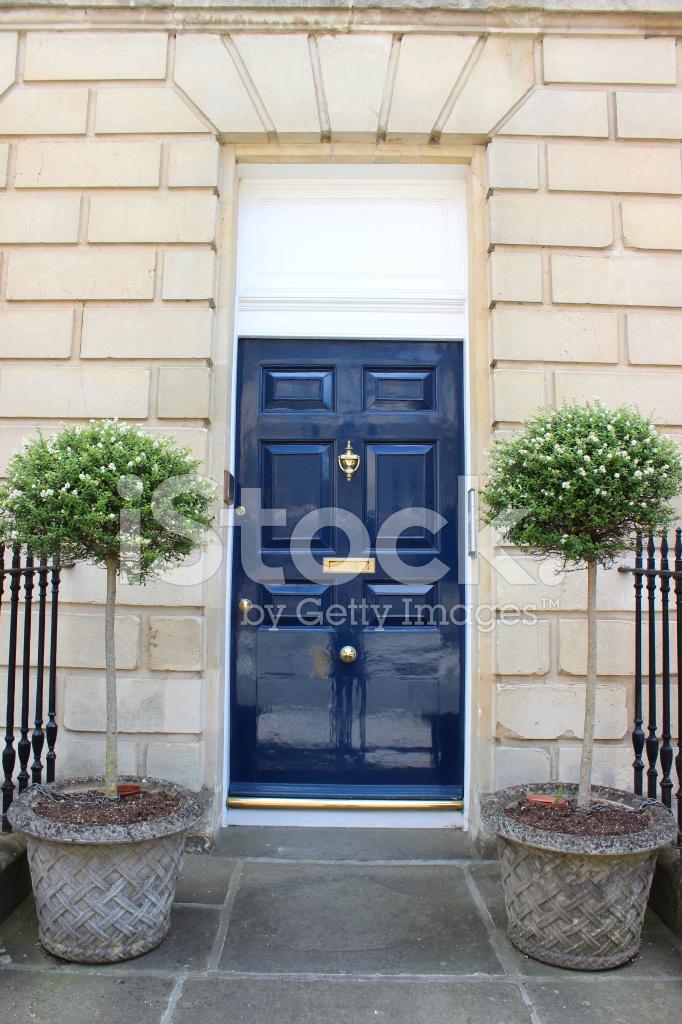 dark blue front door on georgian house standard bay trees