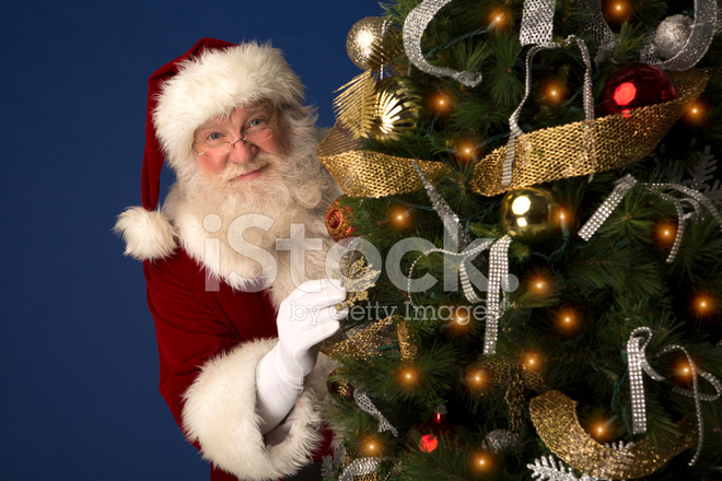 A Christmas.Santa Claus Looking From Behind A Christmas Tree Stock