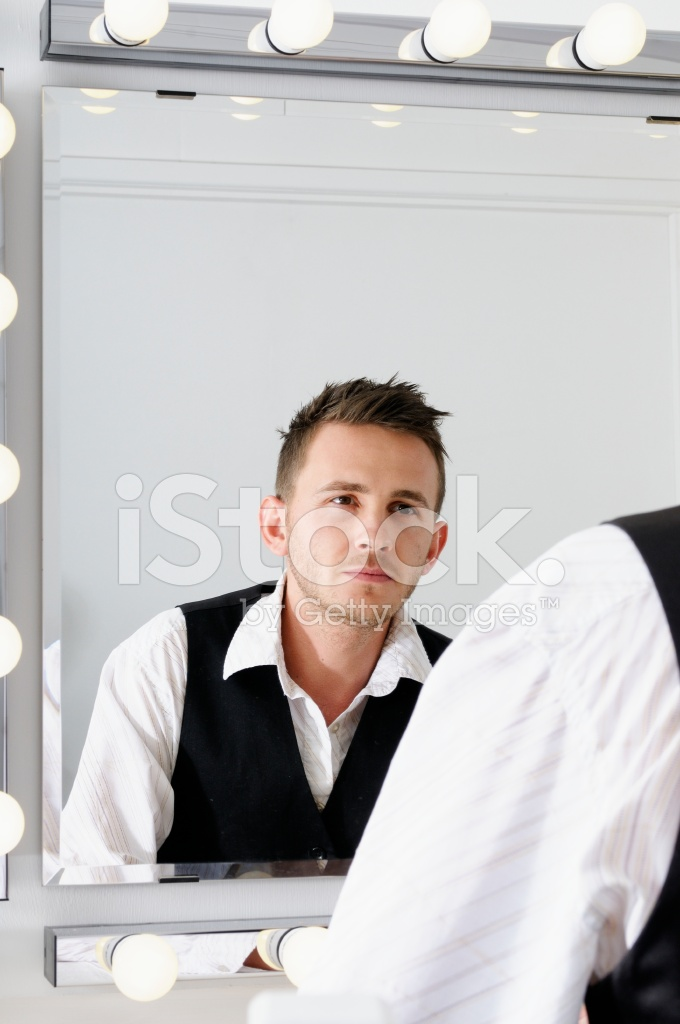 young caucasian man looking into the mirror stock photos