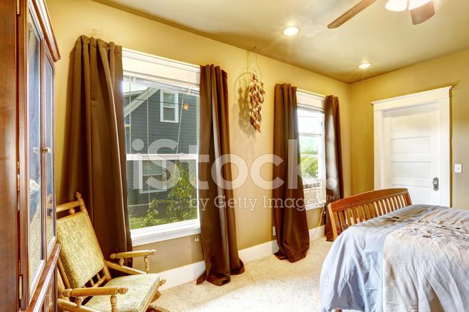 Warme tinten slaapkamer met bruine gordijnen stockfoto s