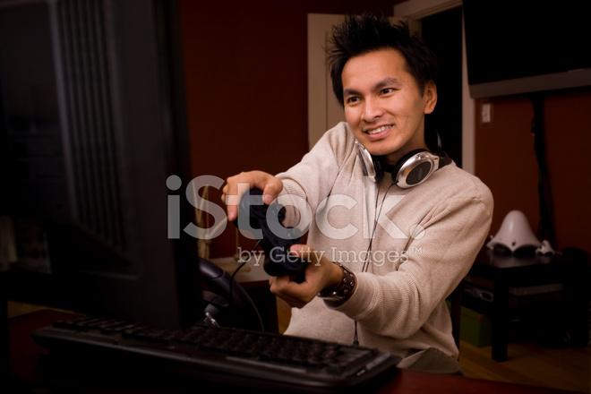 Asiatique bureau gamer souriant À laide de pc télécommande et