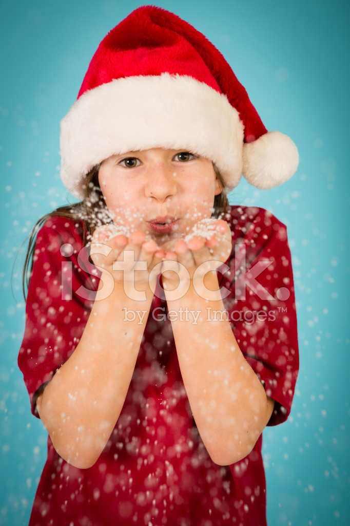d13dc030b2a61 Little Girl Wearing Santa Hat and Blowing Handful of Snow Stock ...