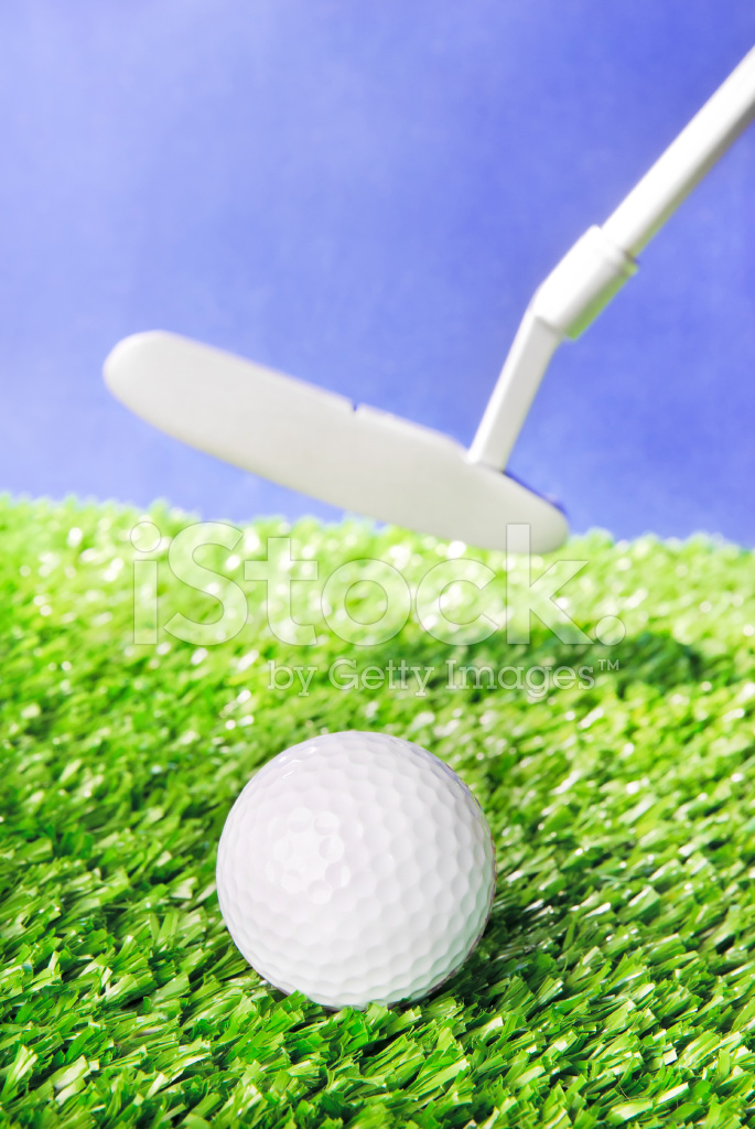 Golf ball and club on green grass against blue sky stock for Fish food golf balls