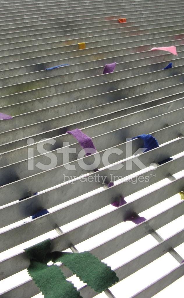 Multi coloured ribbon around metal fence stock photos