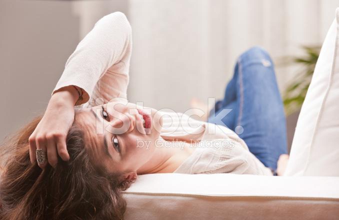 Hübsches Mädchen IN Blue Jeans Beobachten Sie Aus Einem Sofa ...