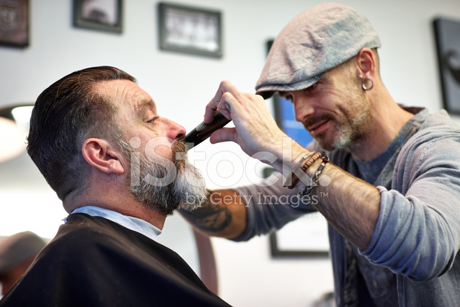 barber trimming beard of a client stock photos. Black Bedroom Furniture Sets. Home Design Ideas