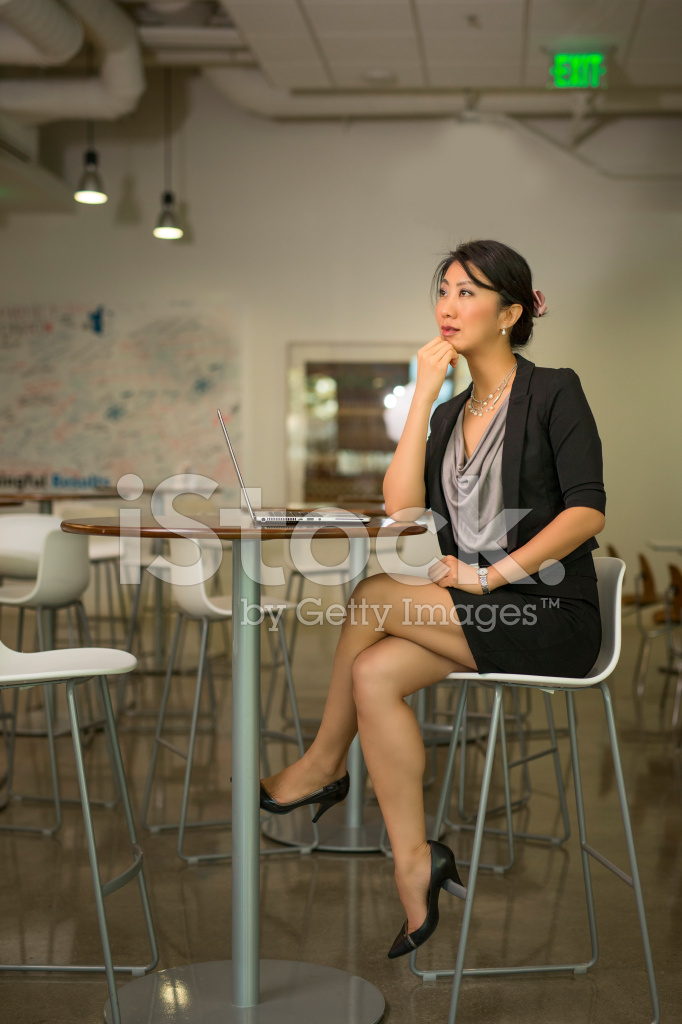 confident businesswoman crossing legs on high chair stock