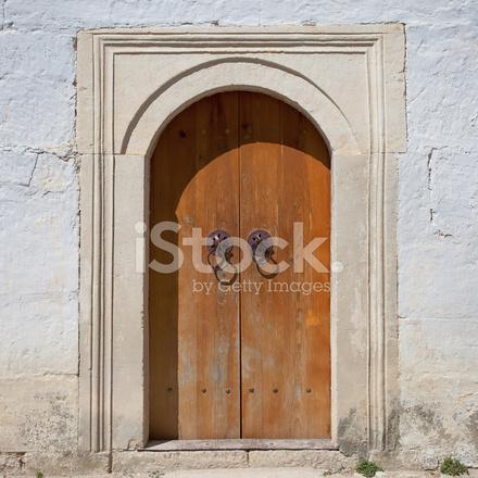 Antico muro in pietra con arco porta di legno fotografie stock ...