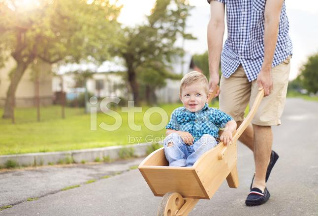 Father Pushing His Son In Wheelbarrow Stock Photos