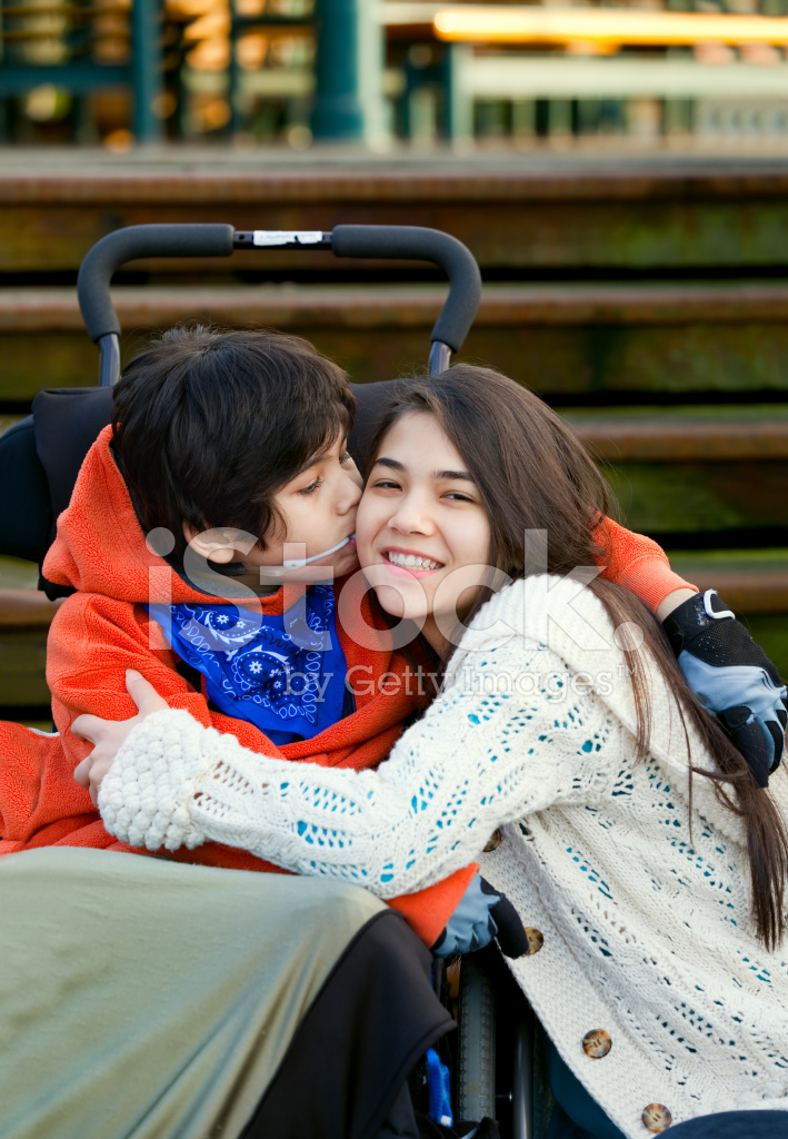 Disabled little boy kissing big sister on cheek stock photos disabled little boy kissing big sister on cheek altavistaventures Images